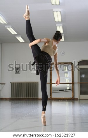 Ballerina with raised leg, to practice a dance hall, Beautiful dancer in a leotard practicing some ballet moves in a dance studio, ballet dancer dancing in the studio woman ballerina rehearsal