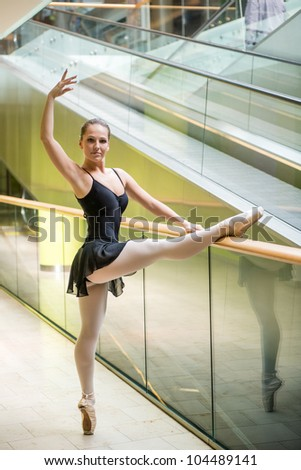 Ballet dancer (ballerina) dancing in modern shopping premises at escalator
