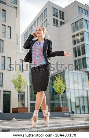 Ballet dancer dressed in business clothes calling with mobile phone - stock photo