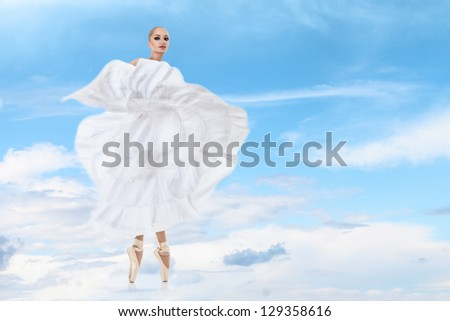 Ballet dancer in beautiful long white dress performing arts against high sky clouds