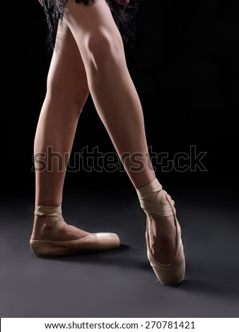 ballet dancer legs pointes on black backgrownd