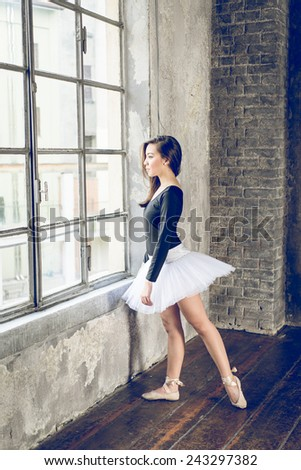 ballet dancer looking outside the window of the gym. concept about fashion and people