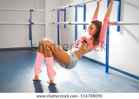 Ballet dancer relaxing after exercise by bar in dance studio