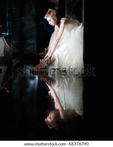 ballet dancer sitting in a tutu stretching on a black reflective background