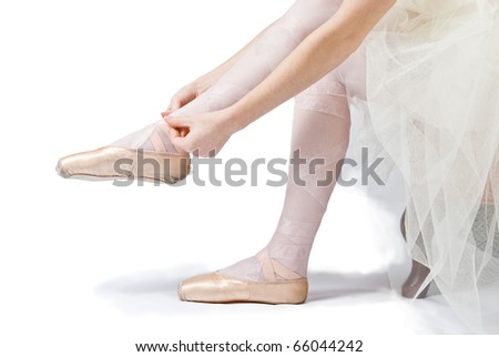 ballet dancer sitting in a tutu tying her shoe on a white background