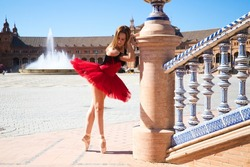 ballet dancer with red tutu leaning on a park railing in seville. The dancer makes different postures and stretches on the railing. Classical ballet concept