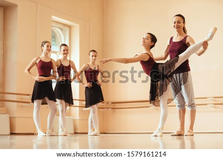Ballet teacher helping ballerina to improve her posture while rehearsing at dance studio. Other ballerinas are standing in the background.