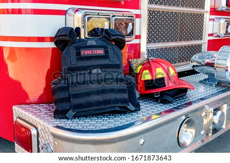 Photo of  Ballistic vest and red firefighter helmet on fire truck bumper. Concept of evolving role of fire department response to mass casualty shooting and terrorism