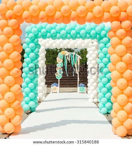 Balloon and paper arches like decorations for wedding ceremony in orange and blue colors