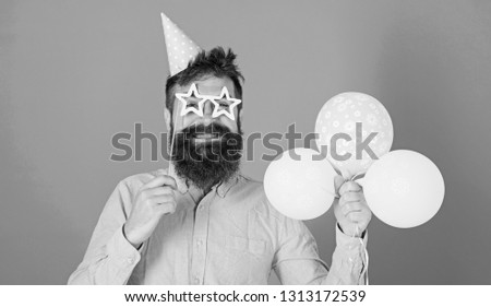 Balloon artist at birthday party. Bearded man entertaining kids at International children day celebration. Smiling man with trendy beard and mustache holding colorful bolloons and party accessories. #1313172539