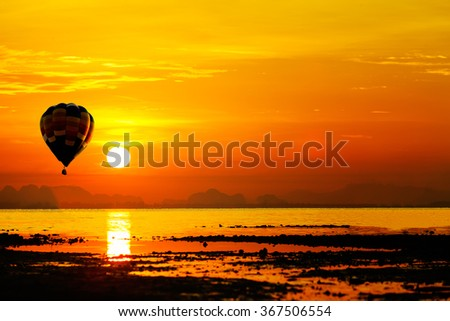 Stock Photo Balloon flying into sunset over the sea.