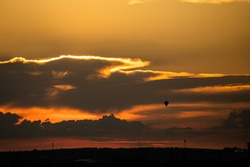 Balloon flying over the city in the sunset light