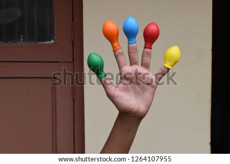 Balloon on finger or kids wearing balloon on fingers  #1264107955