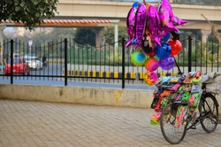 Balloon seller's bike parked on footpath carrying colorful balloons and toys in New Delhi, India