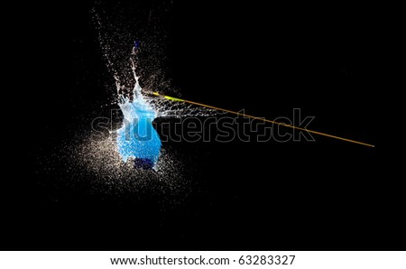 Balloon with water bursting punctured by arrow.High speed photography.
