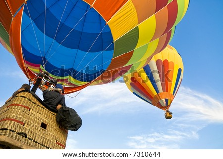 Balloonists running after another hot air balloon in a serene sky