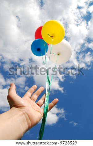 Balloons being released into the clouds on a bright summer day.