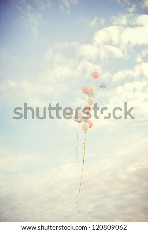 Balloons fly on the sky against clouds