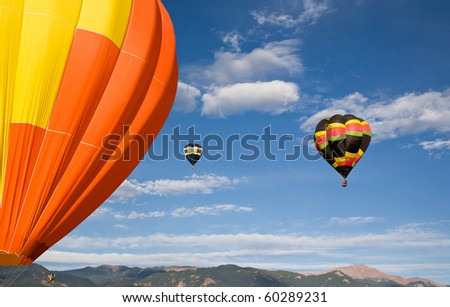 Balloons inflate and ascend into the sky over Pikes Peak.