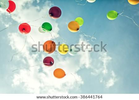 Balloons on cloudy sky