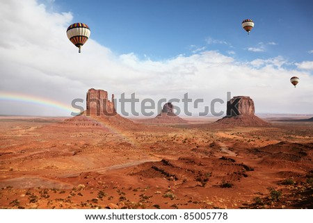Balloons under storm clouds. Monument Valley. The magnificent rainbow over the famous red sandstone Mittens