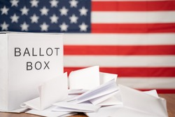 Ballot Box with votes on table before counting with US flag as background concept of Ballot or vote Counting after US election.