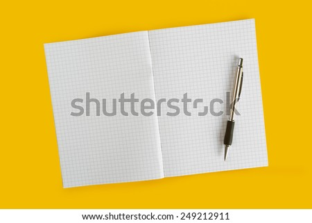 Ballpoint Pen and Blank Paper Notebook with as Business Copy Space on Yellow Background, top view