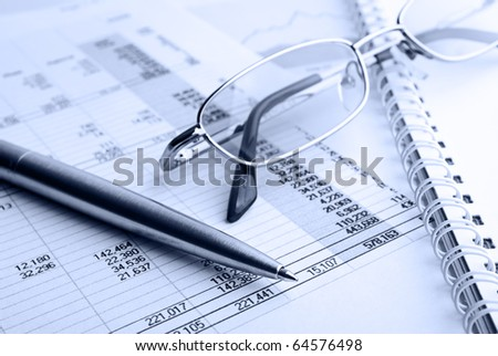 Ballpoint pen,glasses and financial report