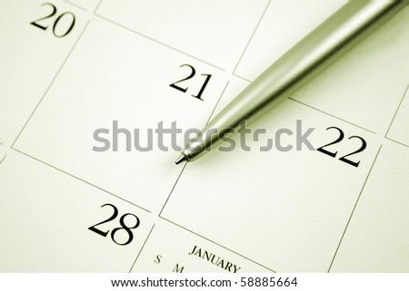 Ballpoint pen on calendar page - stock photo