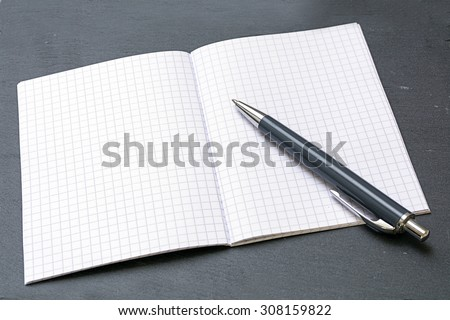 ballpoint pens and a blank notebook with graph paper on a gray blotting pad, copy space
