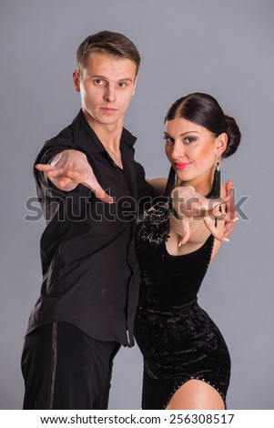 Ballroom dancers dancing. Dancers on a gray background. Man and woman dancing. Man and woman posing in dance position.