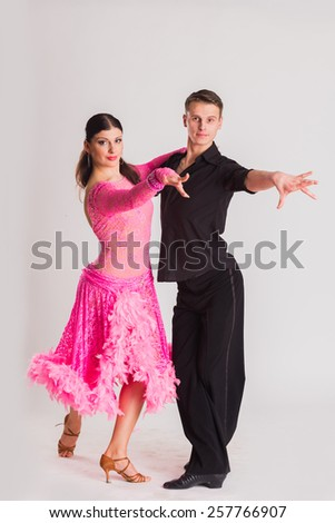 Ballroom dancers dancing. Dancers on a light background. Man and woman dancing. Man and woman posing in dance position.