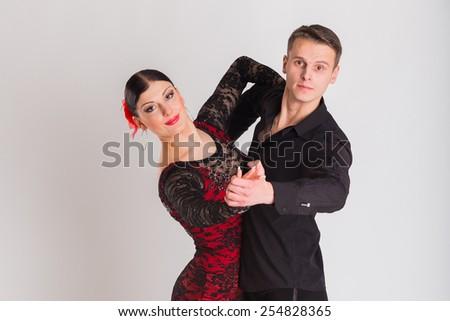 Ballroom dancing. Man and woman posing in dance pose on white. Man and woman dancing ballroom dances. Beautiful man and woman doing the dance steps. Dance poses.
