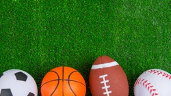 Balls for baseball, american football, basketball, soccer. lie on the green. Outdoor sports championship. Different types of games. copy space