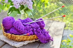 Balls of a lilac yarn and knitting in basket, on wooden table in garden