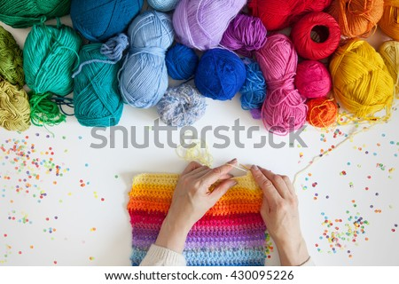Balls of colored yarn. View from above. All the colors of the rainbow. Sample knit. Women\'s hands are knitted. Crochet.