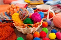 Balls of yarn for knitting. Balls of yarn for knitting in a wicker basket. A cup of tea, a knitting yarn, knitted clothes create coziness. Colorful multi-colored yarn for knitting.