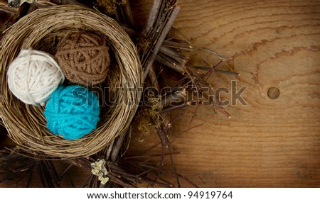 Balls of yarn in a nest easter decoration, on a wooden background, room for copy space.