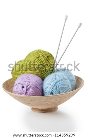 Balls of yarn in basket with knitting needles