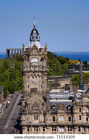 Balmoral clock tower at the East end of Princes Street in Edinburgh captured from the Scott Monument on a bright summer day with Calton Hill visible in the background.