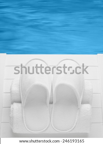 Balneo, spa, hotel, home, wellness slippers with rolled towels on pier with water background - summer, sauna time - space for text