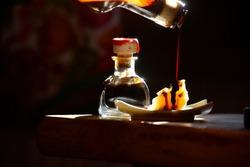 Balsamic vinegar of Modena poured on Parmesan in strong backlight