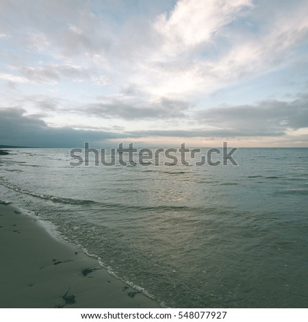 baltic beach in fall with clouds and waves towards deserted dunes. cloudy day - instant vintage square photo