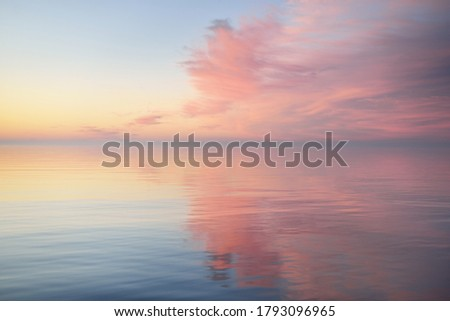Baltic sea after the rain at sunset. Dramatic sky with glowing  pink clouds, symmetry reflections in the water. Abstract natural pattern, texture, background, concept art