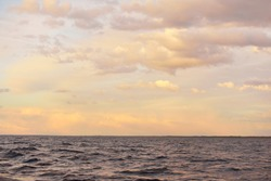 Baltic sea at sunset. Dramatic sky after the storm, soft golden sunlight. Water surface close-up. Nature, environment, ecology, meteorology, cyclone, fickle weather