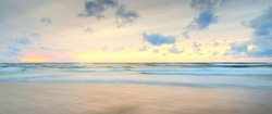 Baltic sea at sunset. Dramatic sky, blue and pink glowing clouds, soft golden sunlight. Waves, splashing water. Picturesque dreamlike seascape, cloudscape, nature. Panoramic view, long exposure