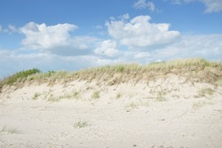 Baltic sea coast. Clear blue sky. Soft sunlight. Beach, sand dunes, pebbles. Pure nature, environmental conservation, ecology, ecotourism, hiking, summer vacations, recreation. Panoramic view