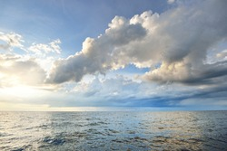 Baltic sea shore after the storm. Dramatic sunset sky, glowing clouds, golden sunlight. Waves, splashing water. Picturesque panoramic scenery, seascape, cloudscape. Nature, environment, ecology
