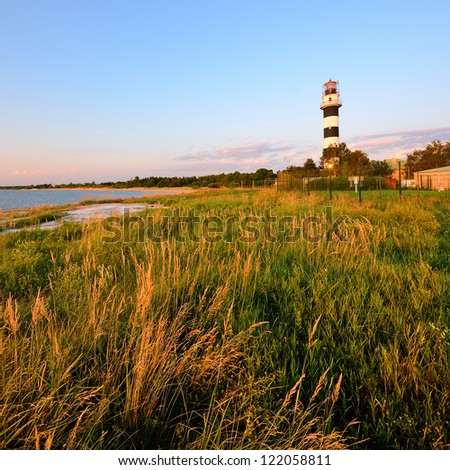 Baltic sea shore with lighthouse at the sunset. Riga, Latvia