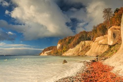 Baltic Sea with coastline on the island of Ruegen. Sunshine on the coast in autumn with clouds and blue sky in the morning. Pirate bay on chalk cliff with trees and stony coast